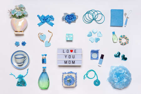 Stylish feminine accessories, flowers, cosmetics, jewelery, perfume in blue pastel colors on white background. Text LOVE YOU MOM on ligthbox, greeting card for mothers day. Flat lay