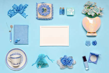Stylish feminine accessories, flowers, cosmetics, gifts and decorative items in blue pastel colors on blue background. Empty white photoframe, mock up. Womens or mothers day concept. Flat lay.