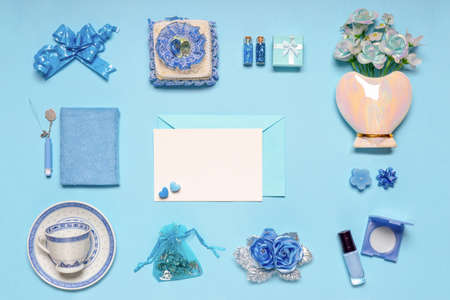 Stylish feminine accessories, flowers, cosmetics, gifts and decorative items in blue pastel colors on blue background. Empty white card for text, mock up. Womens or mothers day concept. Flat lay. Banco de Imagens