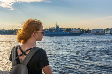 Redhead tween tourist girl on Neva river embankment looking at warships and architectural ensemble in summer evening at sunset. Authentic lifestyle moments, travel concept. Saint Petersburg, Russia.