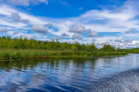 Picturesque summer landscape with northern river and forest in summer cloudy day. Travelling and discovering distant places of Earth. View from floating boat. Chernaya river, Karelia, Russia Stock Photo