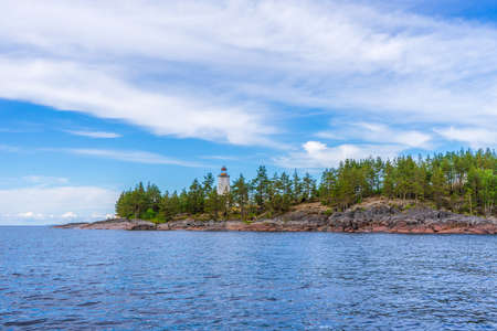 Picturesque summer landscape with northern lake coastline in cloudy day. Travelling and discovering distant places of Earth. View from water. Besov nos cape, Onega lake coast, Karelia, Russia.