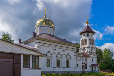 Church to St. Grand Prince Alexander Nevsky in Pudozh after restoration. Orthodox temple and bell tower against northern pine forest and blue sky in summer sunny day. Karelia, Russia.