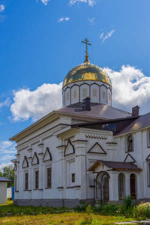 Church to St. Grand Prince Alexander Nevsky in Pudozh after restoration. Orthodox temple against northern pine forest and blue sky in summer sunny day. Karelia, Russia.