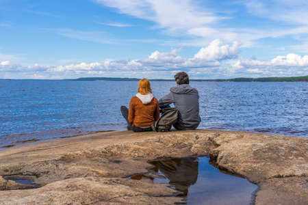 Tourists man and woman sitting on northern lake shore in summer day. People relaxing and admiring beautiful landscape. Travelling and discovering distant places of Earth. Onega lake, Karelia, Russia