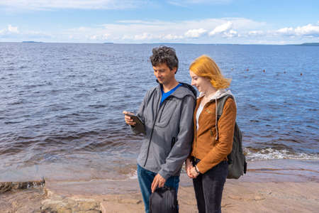 Middle aged man and young lady standing on northern lake shore in summer day. Tourists taking pictures on smartphone. Travelling and discovering distant places of Earth. Onega lake, Karelia, Russia Stock fotó
