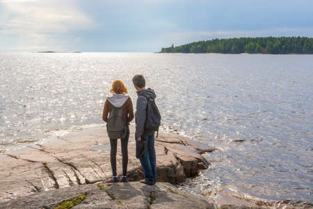 Middle aged man and young lady walking on northern lake shore in summer day. Tourists against picturesque landscape. Travelling and discovering distant places of Earth. Onega lake, Karelia, Russia Stock fotó