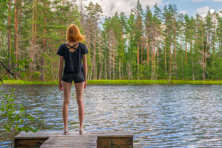 Cute ginger girl standing on wooden planked footway in summer day against beautiful landscape of northern lake and forest. Travelling and discovering distant places of Earth. Karelia, Russia