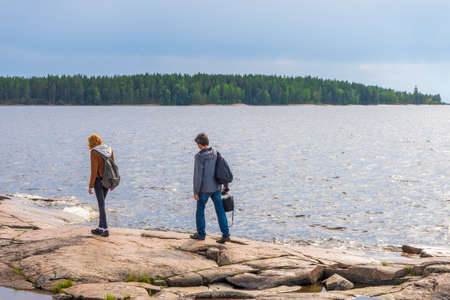 Middle aged man and young lady walking on northern lake shore in summer day. Tourists against picturesque landscape. Travelling and discovering distant places of Earth. Onega lake, Karelia, Russia. Stock fotó