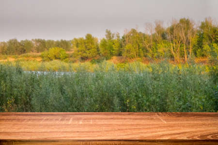 Empty wooden table with blurred summer background of riverside at sunset. Can be used for display or montage products