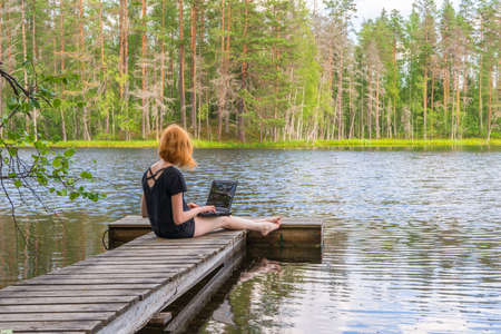 Cute ginger girl sitting on wooden planked footway and working with laptop in summer day against beautiful landscape of northern lake and forest. Freelance, work and travel concept. Karelia, Russia.