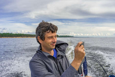 Handsome middle-aged man sitting at boat stern, floating along northern lake and using smartphone on beautiful landscape background in summer day. Travel concept. Onega lake, Karelia, Russia.