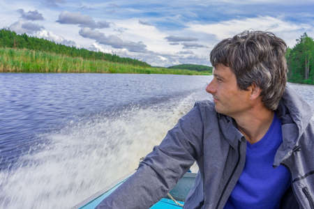 Handsome middle-aged man sitting at boat stern, floating along northern river and relaxing on beautiful landscape background in summer day. Travel concept. Chernaya river, Karelia, Russia.