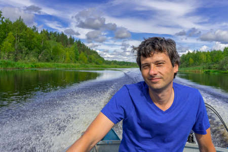 Handsome middle-aged man sitting at boat stern and floating along northern river on beautiful landscape background in summer day. Travel concept. Chernaya river, Karelia, Russia.
