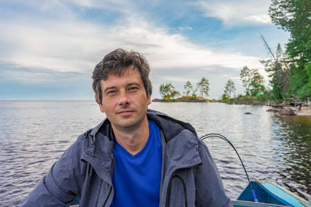 Handsome middle-aged man sitting at boat stern and floating along northern river on beautiful landscape background at sunset. Travel concept. Onega lake, Karelia, Russia.