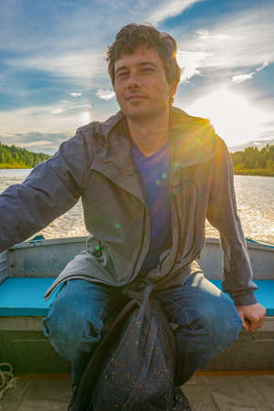 Handsome middle-aged man sitting at boat stern and floating along northern river on beautiful landscape background at sunset. Travel concept. Chernaya river, Karelia, Russia. Stock fotó