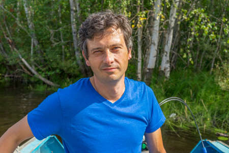 Handsome middle-aged man sitting at boat stern and floating along northern river on beautiful landscape background in summer sunny day. Travel concept. Chernaya river, Karelia, Russia.