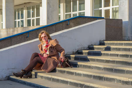Attractive middle-aged woman wearing stylish coat and shoes sitting with bag on stairs step of office building in early spring at sunset. Street city portrait, fashion urban outfit. Stock fotó