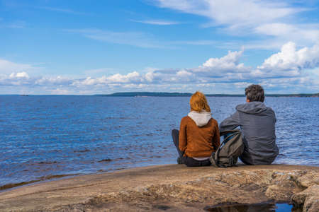 Tourists man and woman sitting on northern lake shore in summer day. People relaxing and admiring beautiful landscape. Travelling and discovering distant places of Earth. Onega lake, Karelia, Russia.