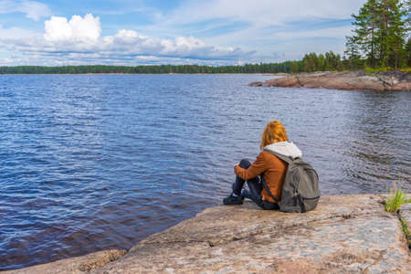 Young tourist lady sitting on northern lake shore in summer day. Teenage girl relaxing and admiring beautiful landscape. Travelling and discovering distant places of Earth. Onega lake, Karelia Russia