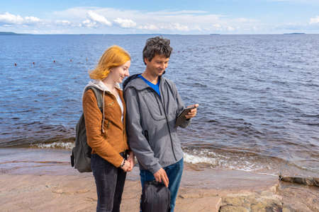 Middle aged man and young lady standing on northern lake shore in summer day. Tourists taking pictures on smartphone. Travelling and discovering distant places of Earth. Onega lake, Karelia, Russia.