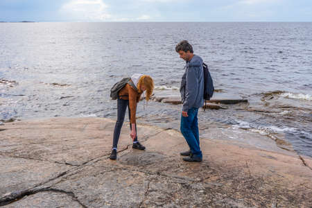 Middle aged man and young lady walking on northern lake shore in summer day. Tourists exploring ancient petroglyphs. Travelling and discovering distant places of Earth. Onega lake, Karelia, Russia.