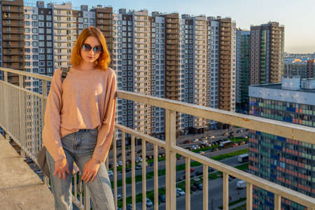 Tween redhead girl in pullover, jeans and sunglasses standing on balcony against high-rise multi-storey residential building at sunset. Beautiful look, fashionable city street outfit, teenage fashion. Stock fotó