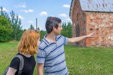 Middle aged dark-haired tourist man showing direction by hand for young redhead lady. Traveler asking path from stranger on background of ancient landmark in summer day.