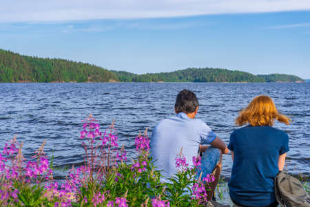 Tourists dark-haired man and redhead young woman sitting on stones on shore of lake bay in sunny summer evening. People resting and admiring beautiful landscape of Ladoga lake. Karelia, Russia.