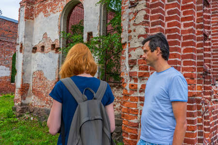 Tourists adult man and teenage girl exploring ruined Lutheran church in Lahdenpohja, Karelia, Russia. Cognitive tourism, active leisure, summer travel concept. 스톡 콘텐츠