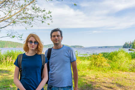 Tourists adult man and teenage girl posing against beautiful landscape in summer sunny day. Portraits of father and daughter on Ladoga lake shore. Travelling and discovering places. Karelia, Russia. 스톡 콘텐츠