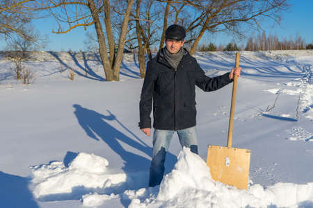 Handsome middle-aged caucasian man cleaning snow on household plot in sunny day. Man with shovel paving path from country house to road. Winter active leisure concept. 스톡 콘텐츠