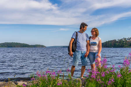 Tourists middle aged man and woman posing against beautiful landscape in summer sunny day. Couple standing on Ladoga lake shore. Travelling and discovering distant places of Earth. Karelia, Russia. 스톡 콘텐츠