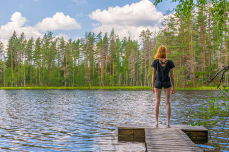 Cute ginger girl standing on wooden planked footway in summer day against beautiful landscape of northern lake and forest. Travelling and discovering distant places of Earth. Karelia, Russia.
