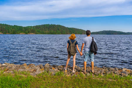 Tourists man and woman standing on shore of lake bay in sunny summer evening. People admiring beautiful landscape of Ladoga lake. Travelling and discovering distant places of Earth. Karelia, Russia.