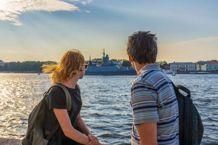 Middle-aged dark-haired man and young redhead lady on Neva river embankment looking at warships and architectural ensemble in summer evening at sunset. Travel concept. Saint Petersburg, Russia. 스톡 콘텐츠