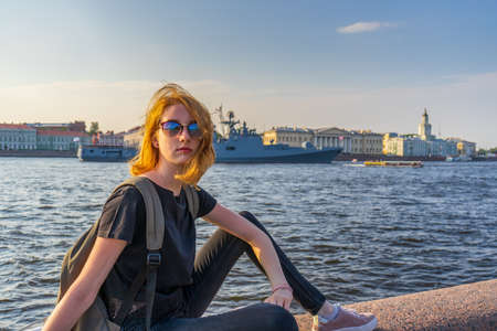 Redhead teen tourist girl on Neva river embankment posing against warship and architectural ensemble in summer evening at sunset. Authentic lifestyle moments, travel concept. Saint Petersburg, Russia.