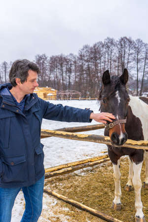 Handsome middle-aged man patting horse at ranch in snowy day. Winter weekend at farm, trip to countryside. Healthy lifestyle, active leisure, authentic moments. 스톡 콘텐츠