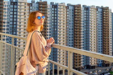Tween redhead girl in pullover, jeans and sunglasses standing on balcony against high-rise multi-storey residential building at sunset. Beautiful look, fashionable city street outfit, teenage fashion. Фото со стока