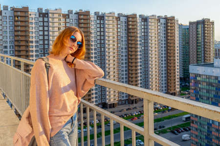 Tween redhead girl in pullover, jeans and sunglasses standing on balcony against high-rise multi-storey residential building at sunset. Beautiful look, fashionable city street outfit, teenage fashion. 스톡 콘텐츠