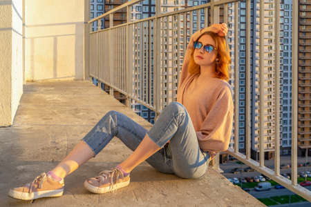 Tween redhead girl in pullover, jeans and sneakers sitting on balcony against high-rise multi-storey residential building at sunset. Beautiful look, fashionable city street outfit, teenage fashion. 스톡 콘텐츠