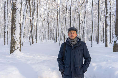 Portrait of handsome middle-aged man walking in winter snowy park or forest. Attractive man in jacket, scarf and cap looking at camera. Winter mood, authentic lifestyle concept, stylish male outfit.