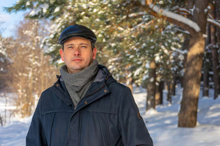 Portrait of handsome middle-aged man against beautiful winter landscape. Man walking in snowy forest in sunny frosty day. Human and nature, winter holidays, weekend at countryside concept. 스톡 콘텐츠