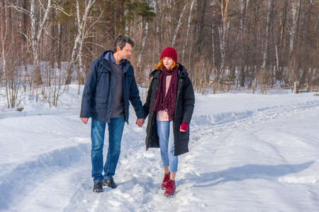Handsome man and attractive young woman walking along snowy country road in sunny day. Beautiful look, male and female fashion, winter outfit. Winter holidays, weekend at countryside concept.