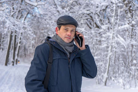 Handsome middle-aged man walking in winter snowy park or forest. Attractive man in jacket, scarf and cap talking on mobile phone. Winter mood, authentic lifestyle concept, stylish male outfit. 스톡 콘텐츠