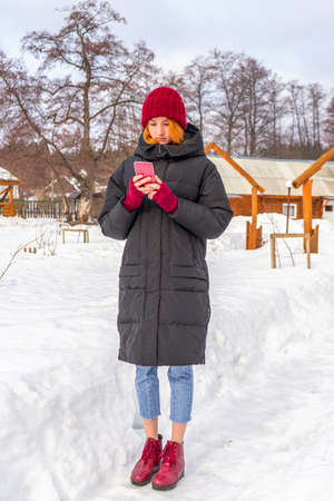 Teen cute girl in black down jacket, blue cropped jeans, burgundy hat, boots and fingerless gloves standing outdoor against winter rural landscape. Weekend at countryside, teenage fashion concept.