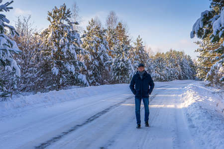 Handsome middle-aged man against beautiful winter snowy landscape. Man walking along forest road in sunny frosty day. Human and nature, winter holidays, weekend at countryside concept.