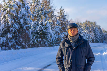Portrait of handsome middle-aged man against beautiful winter landscape. Man walking along forest road in sunny frosty day. Human and nature, winter holidays, weekend at countryside concept.