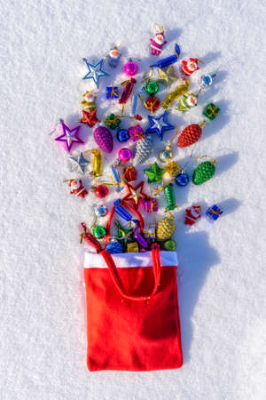 Red bag with many colorful new year toys lying on white fresh snow. Santa Claus scattered bag of gifts. Merry Christmas and Happy New Year. Greeting card for winter holidays. Top view. 스톡 콘텐츠