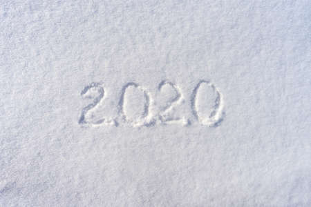 Text 2020 written on white fresh snow in sunny winter day. Merry Christmas and Happy New Year. Winter holiday concept.